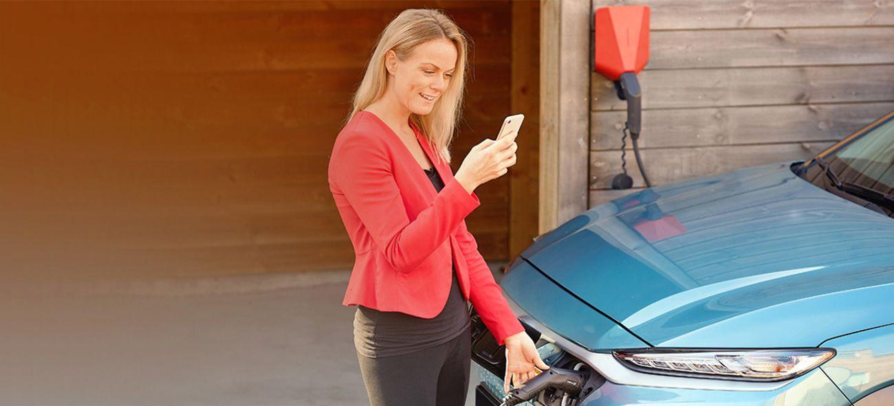 En dame som lader bilen sin og ser på mobilen samtidig.