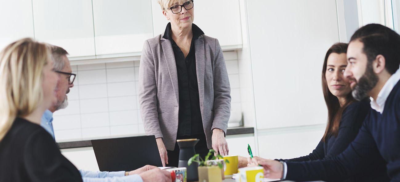 En dame styrer et møte med fire deltagere.