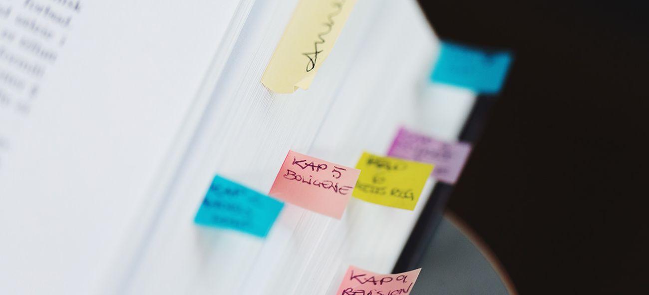 En lovbok med fargerike notatlapper i kanten.