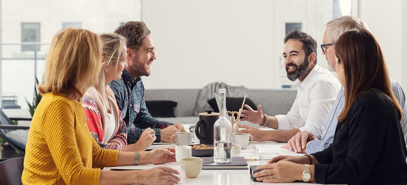 Seks personer som snakker og ler rundt et bord.