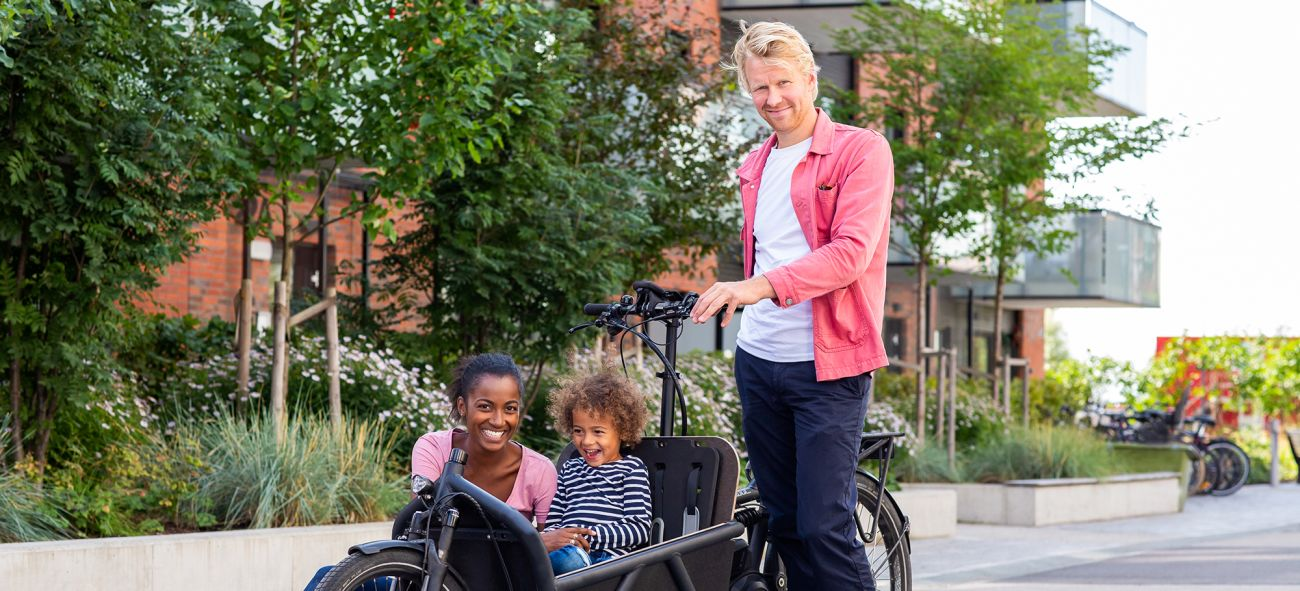 En mor, datter og far med en lastesykkel