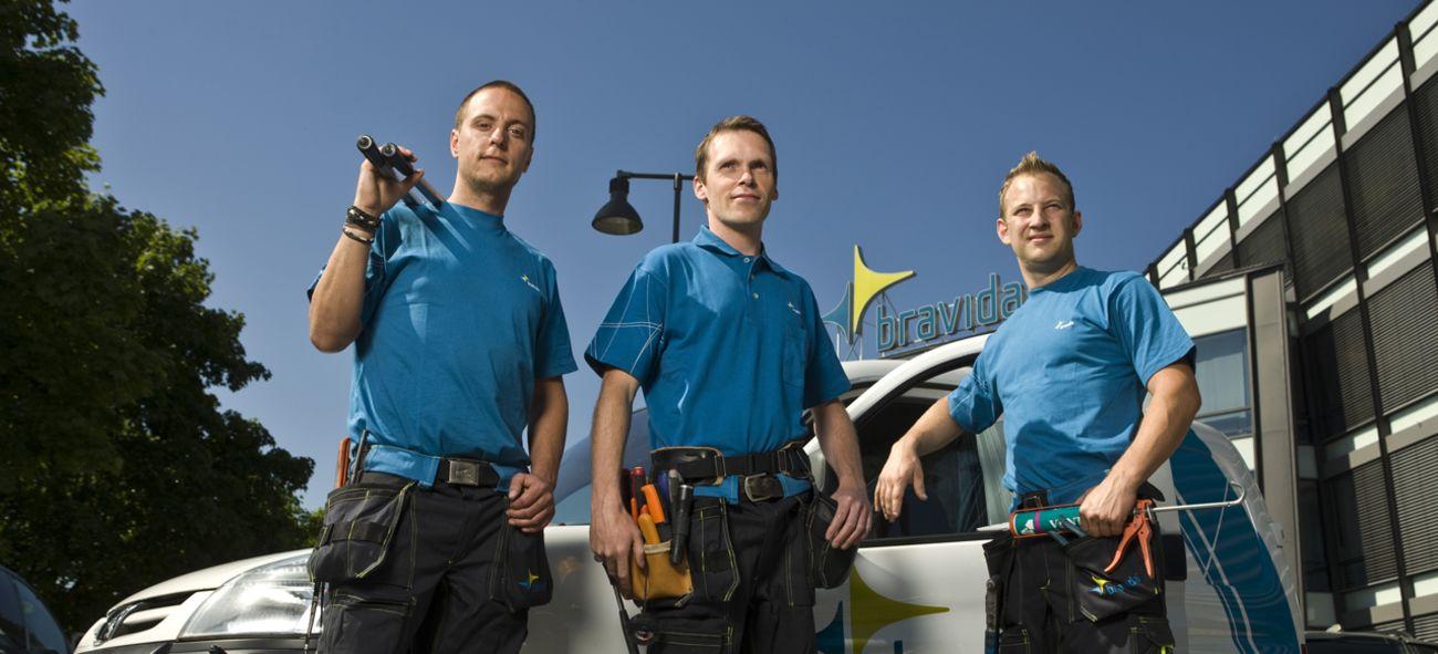 Bravida-ansatte i blå skjorter poserer foran en bil