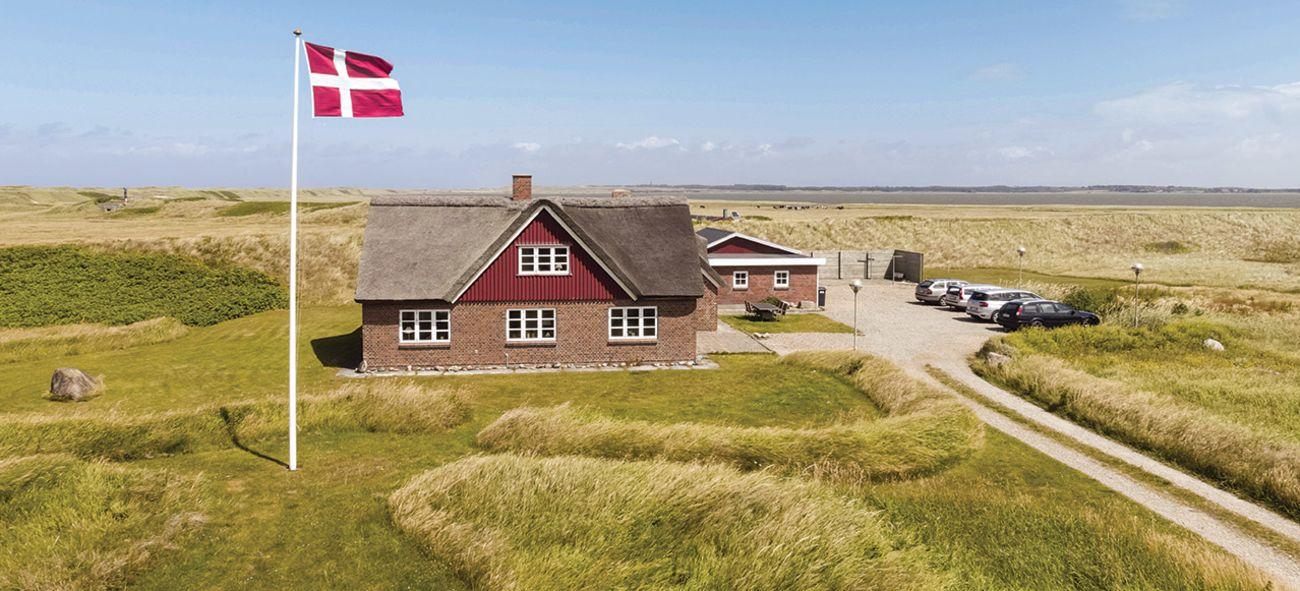 Et hus på et ellers øde område med det danske flagget heist.
