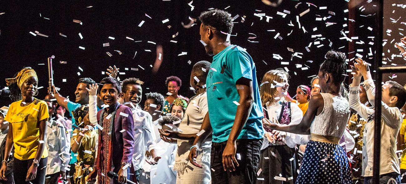 Fargespillere på scenen med konfetti i dalende i lufta