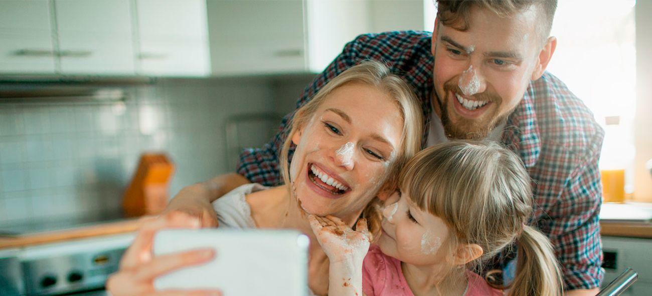 Familie med mor, datter og far som tar selfie med mobilen.