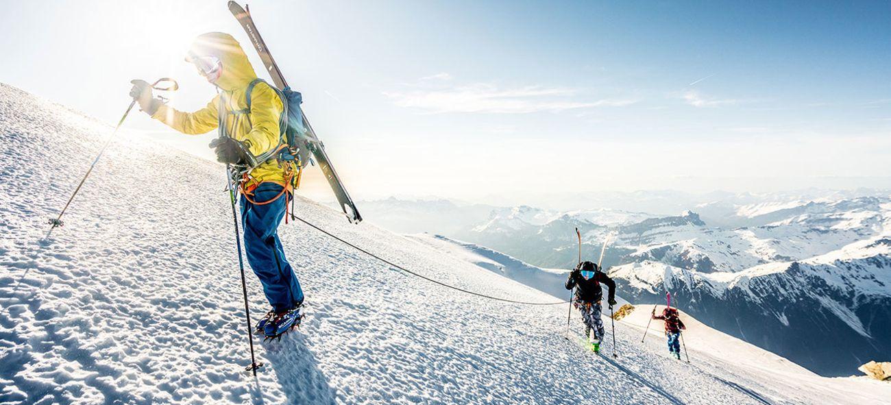 Tre frikjørere på vei opp en snøkledd fjelltopp