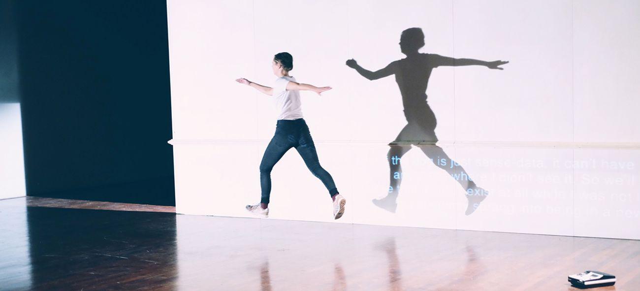 En kvinnelig danser i olabukser og hvit t-skjorte i luftig svev over scenegulvet.