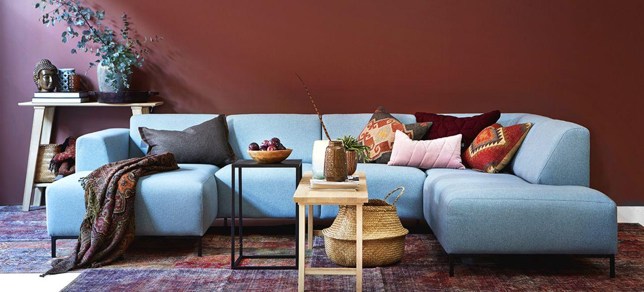 En blå sofa foran en rød vegg med diverse interiør og pynt