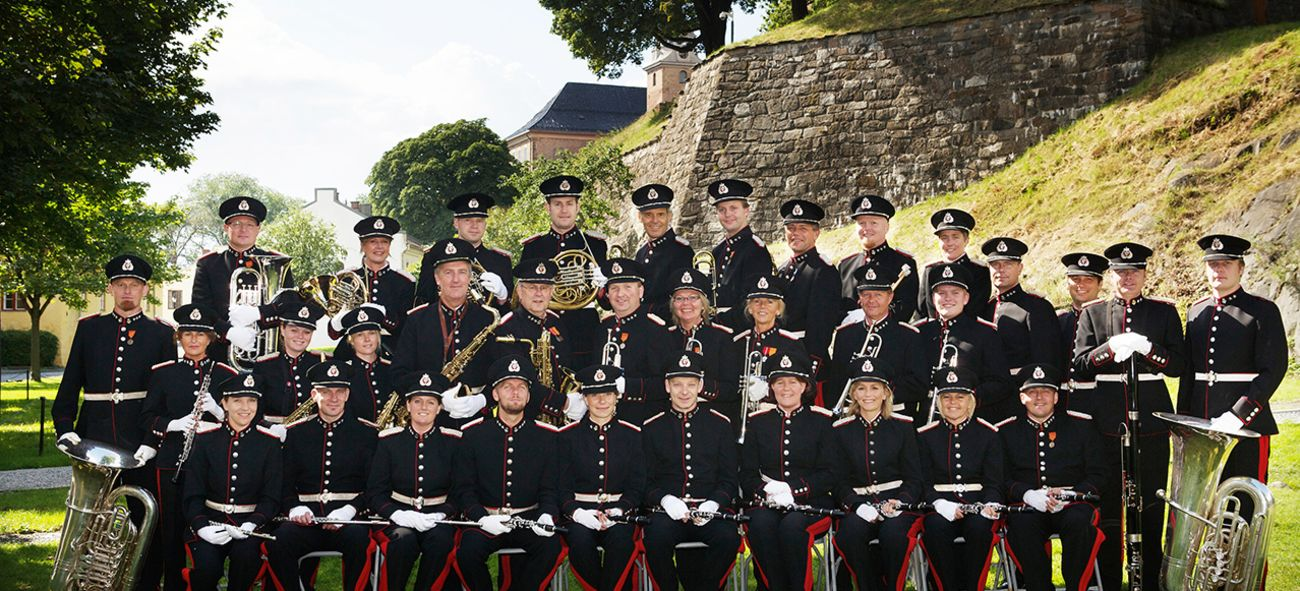 Musikerne i Stabsmusikken, utendørs på plenen ved Akershus festning. Alle kledd i uniform.