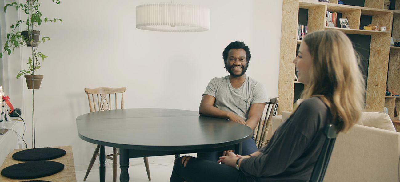 Mann og kvinne sitter rundt et bord og ler