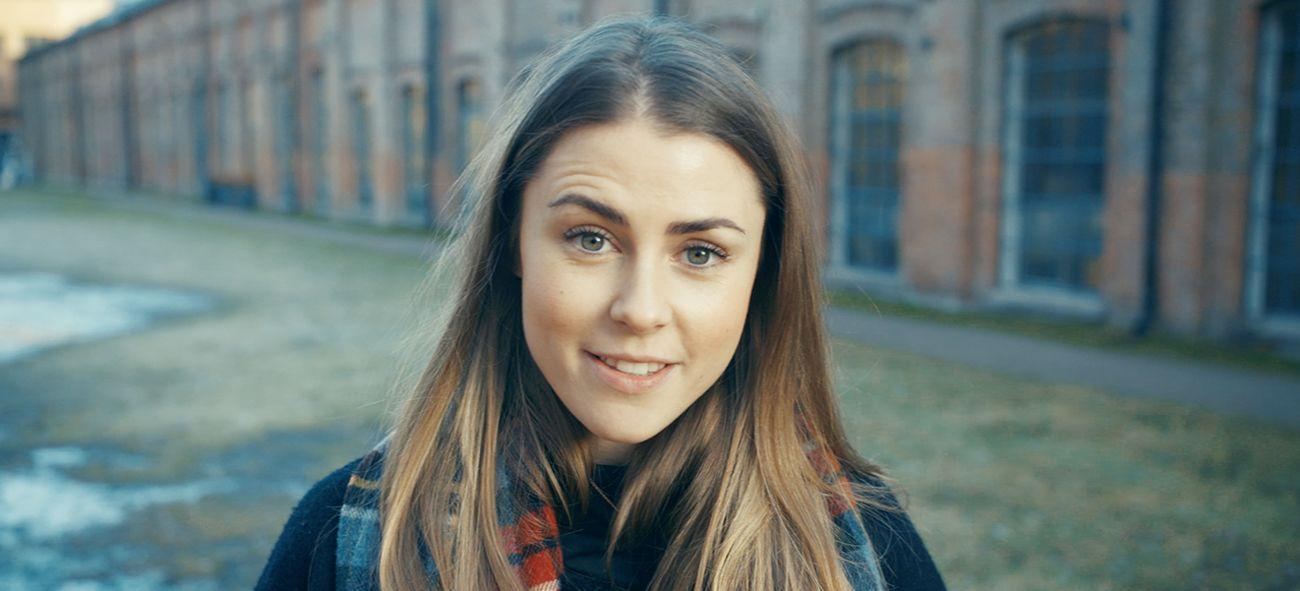 Kvinne med brunt hår ser i kamera og smiler