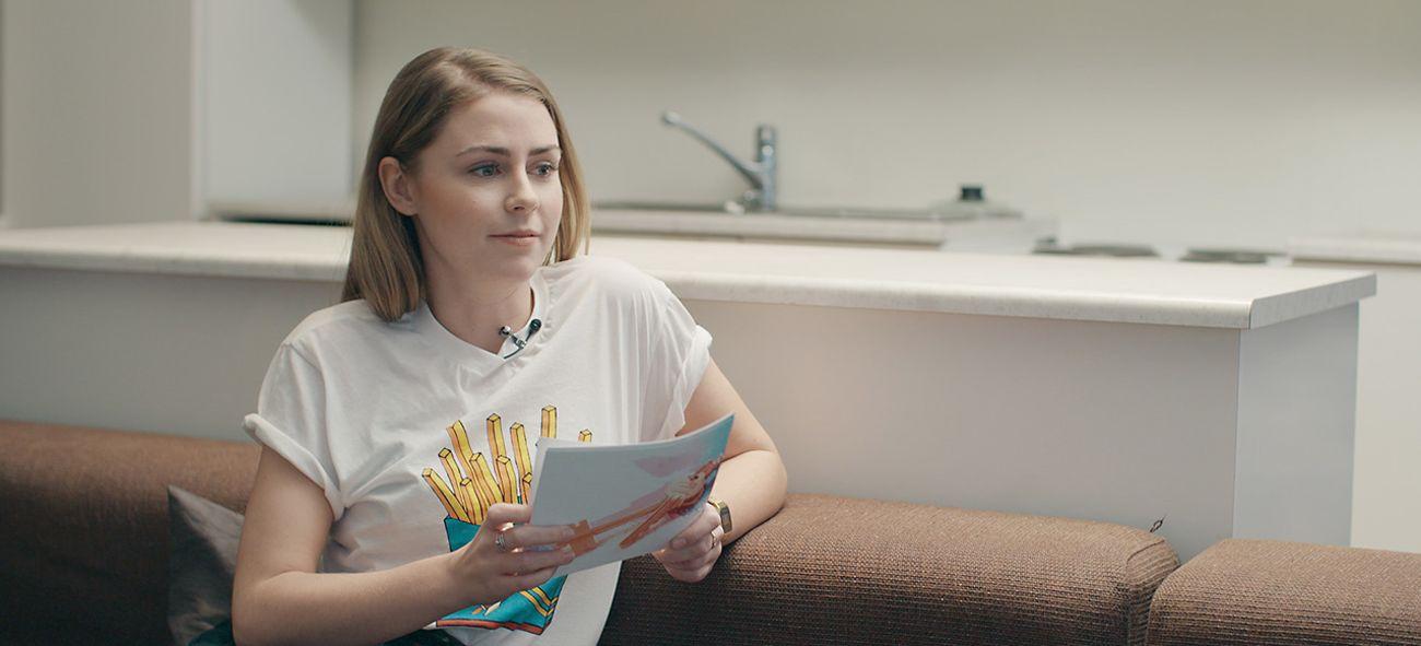Kvinne sitter i en brun sofa og holder et prospekt