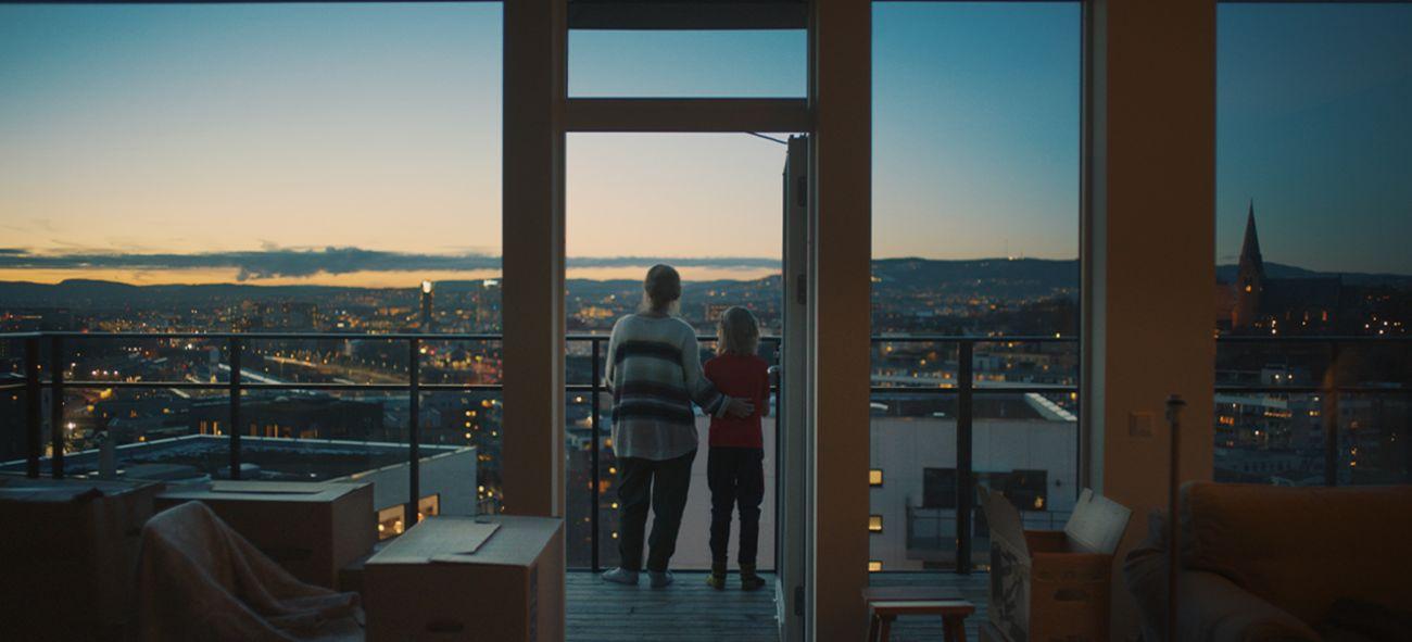 Illustrasjonsfoto av mor og datter på en balkong med utsikt over en by.