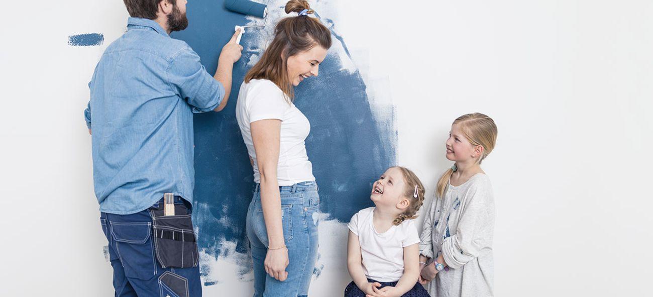 Familie som maler veggen blå.