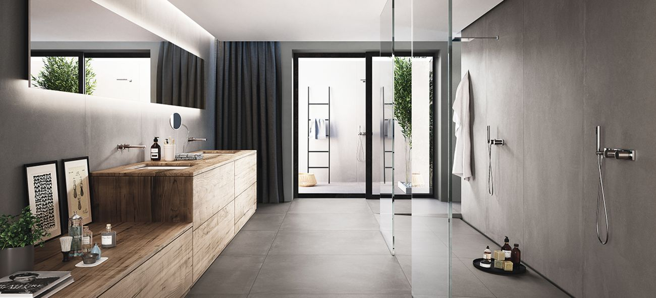 Et luftig baderom med minimalistisk innredning og store, matte fliser i betong-farve.