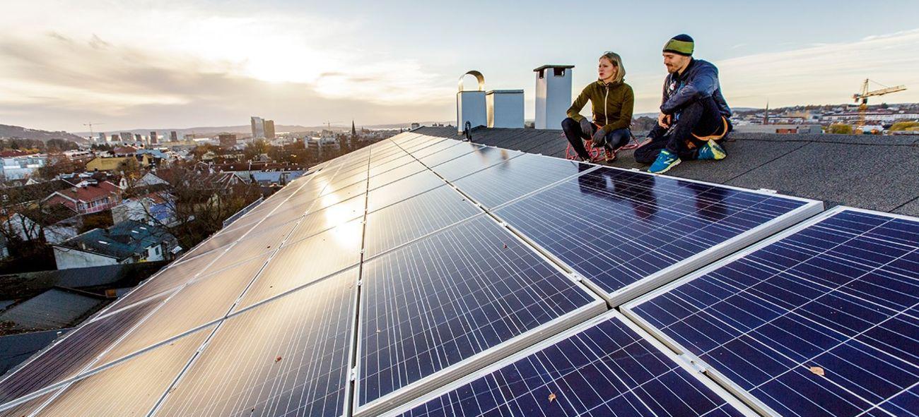 To mennesker sitter på et tak med solseller