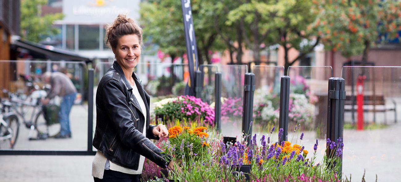 Smilende kvinne arrangerer blomster i blomsterkasse
