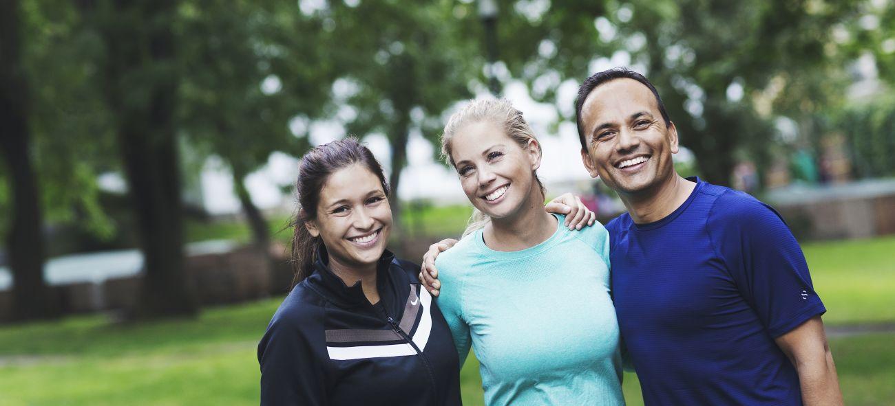 tre OBOS anställda poserar i en park