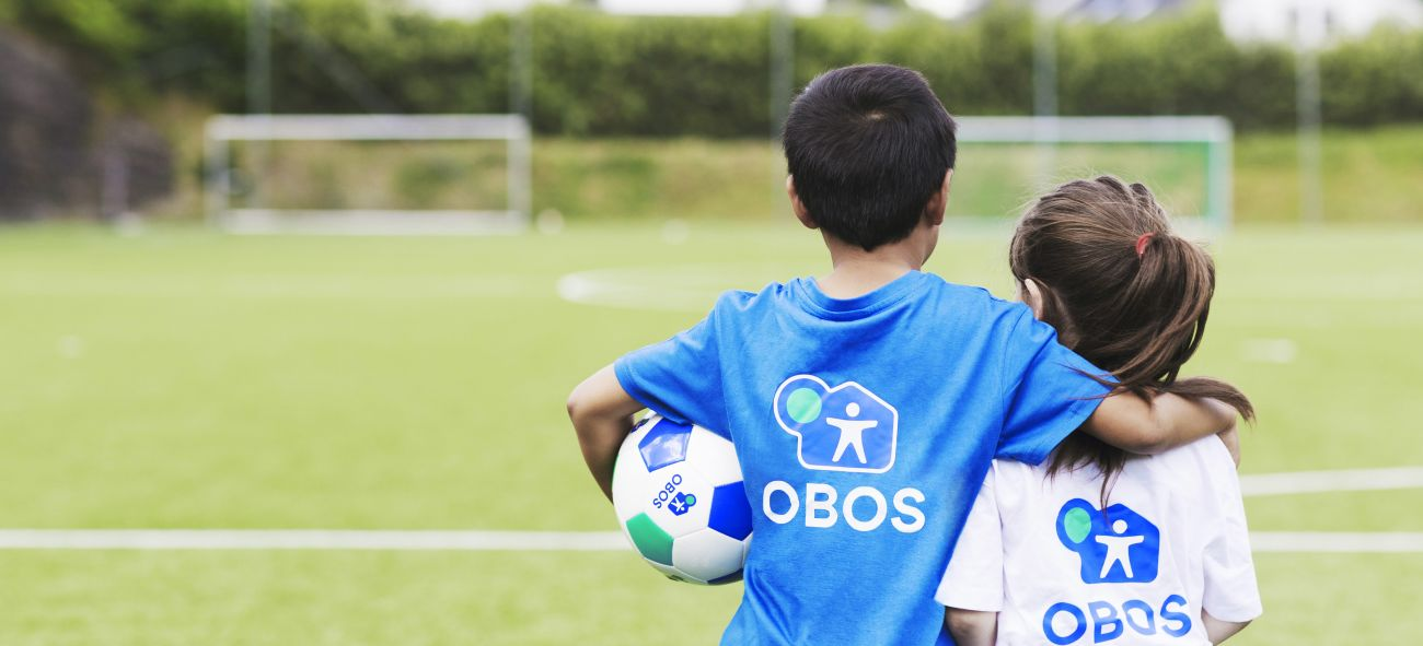Två barn i OBOS-t-shirt som tittar mot ett fotbollsmål