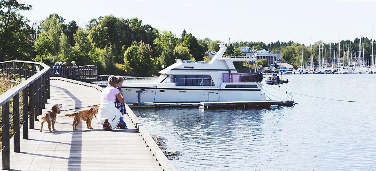 Bildet viser en kvinne og et barn med hund som går lands byggekanten på Fornebu. Båter i bakgrunnen