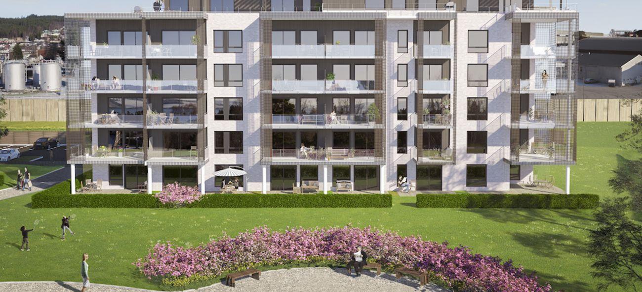 Bilde av boligblokk med store terrasser og grøntområde foran