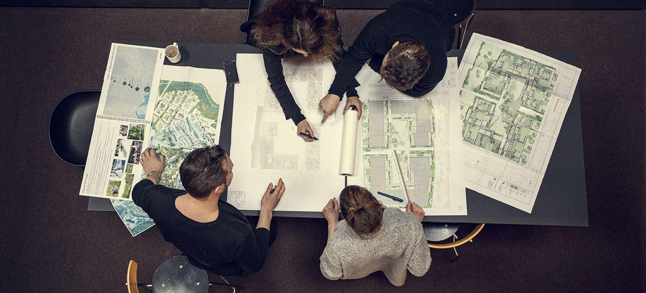 Bilde tatt ovenfra og viser arkitekter sittende ved et bord hvor de jobber med tegninger