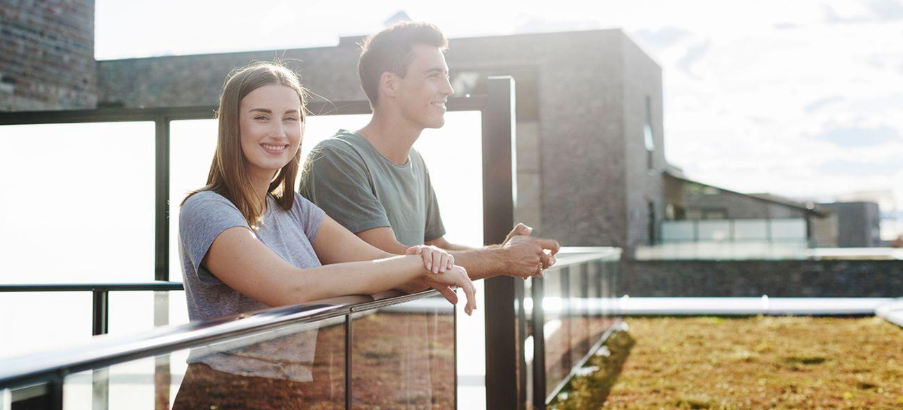 Bilde av et ungt par som står på en terrasse og smiler