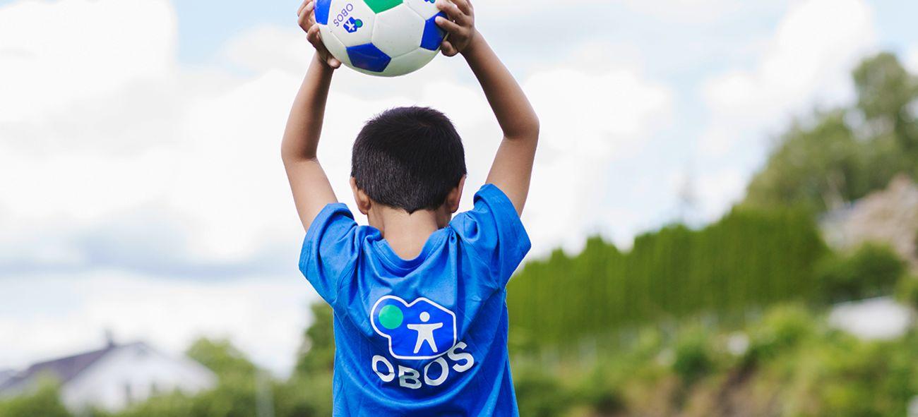 en pojke håller en fotboll i handen