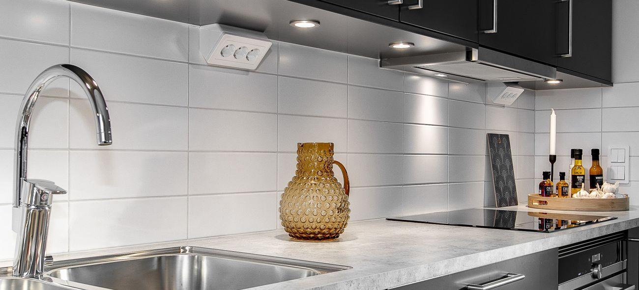 En vattenkanna i glas står på en grå marmorskiva i ett OBOS-kök