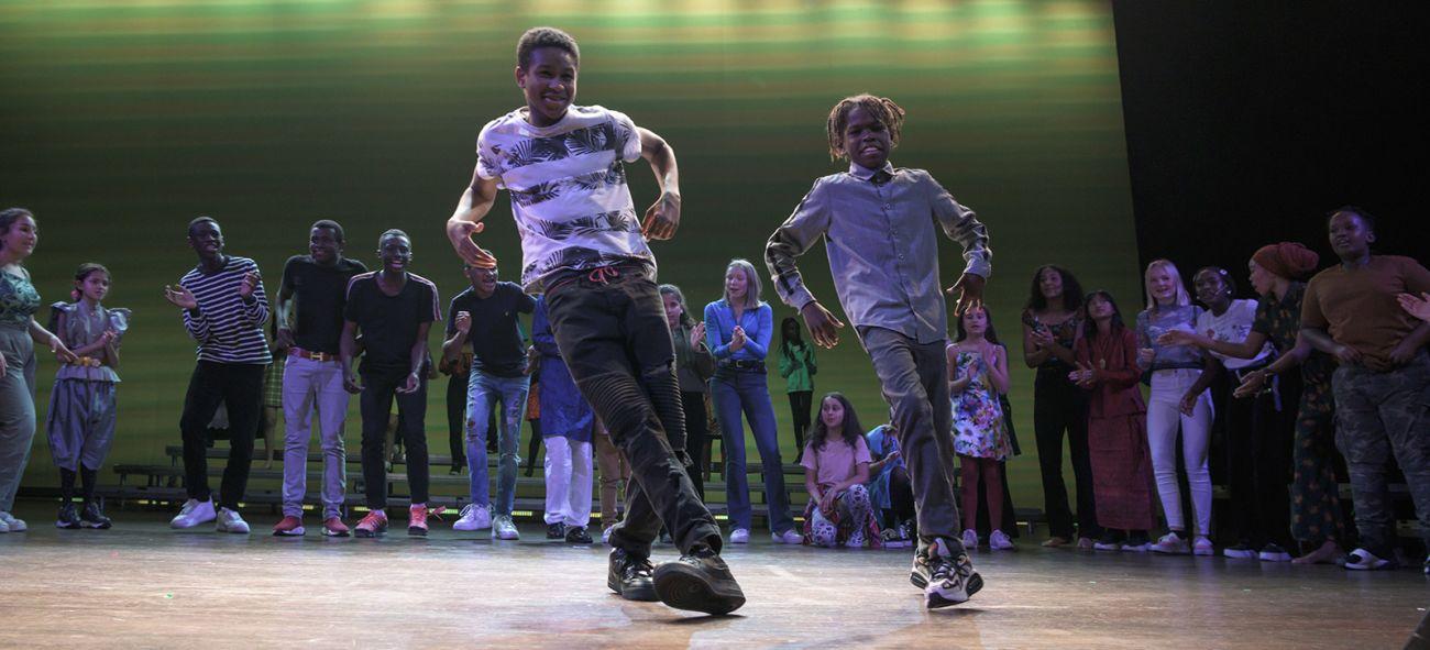 To dansere i front på scenen med ensemble bak