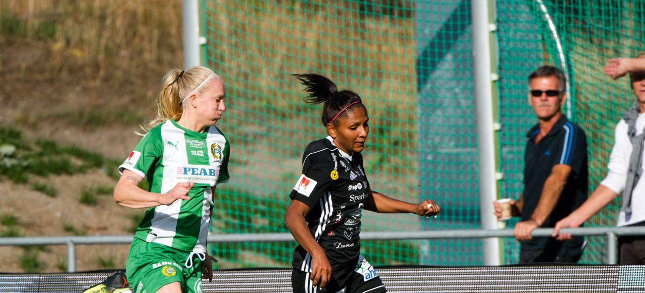två tjejer i motsatta lag springer med en boll på fotbollsplan