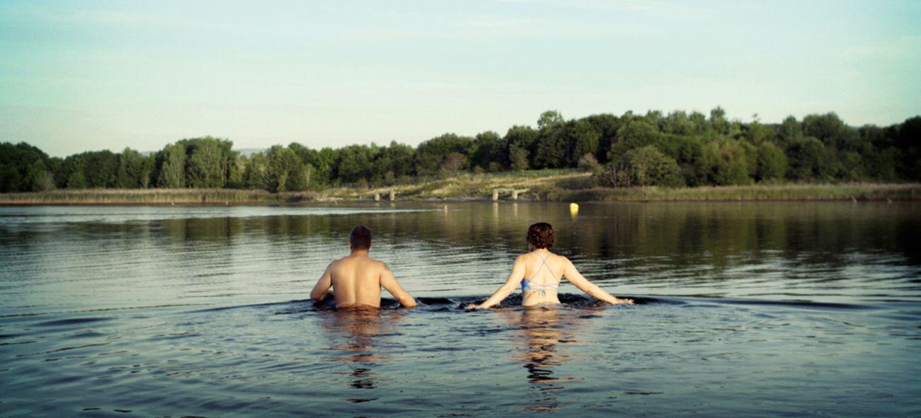 Bildet viser en mann og en kvinne som tar et bad i sjøen på Fornebu.