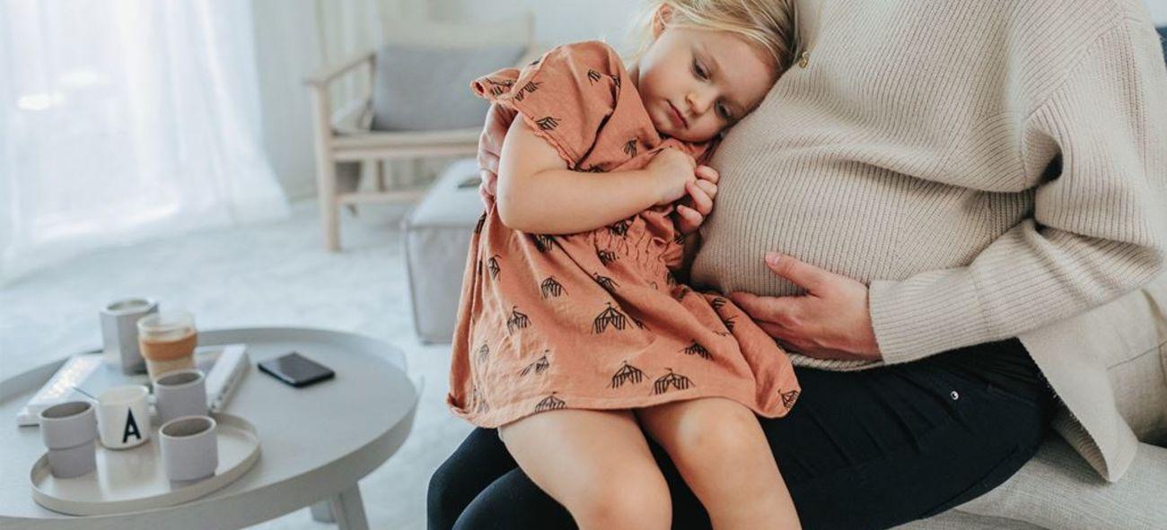Gravid mamma sitter med dotter i knä