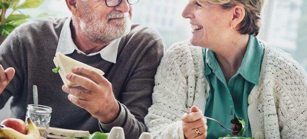ett äldre par tittar på varandra när de äter frukost