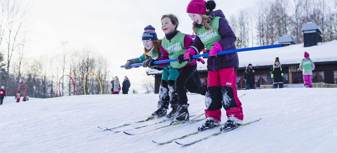 Tre barn på ski som holder i en stang