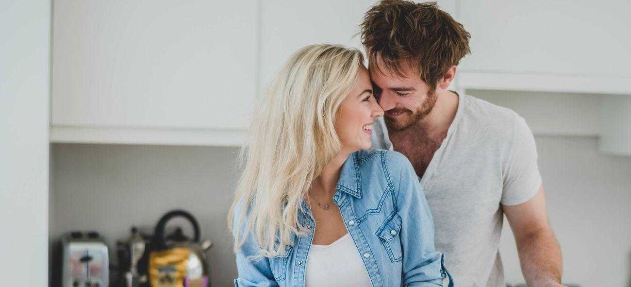 Kvinna och man står i köket och skär grönsaker