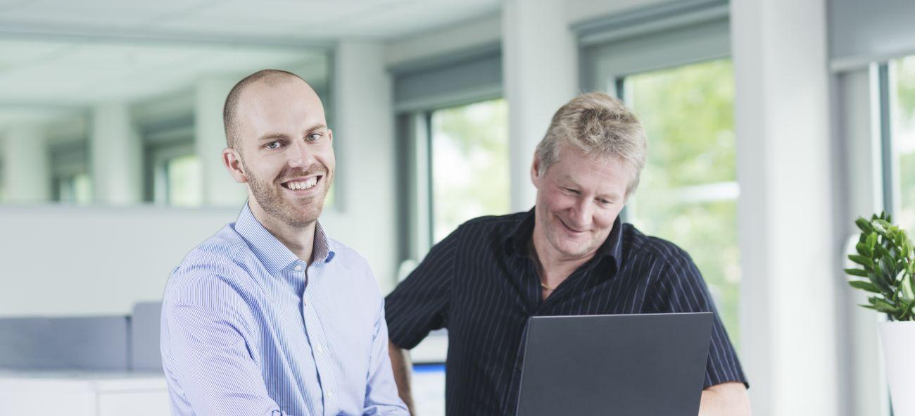 To menn står foran laptop i kontorlandskap