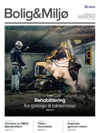 Mann i garasje med hjelpm og maske og fjernkontroll, som fjernstyrer en borremaskin i forbindelse med rehabilitering.