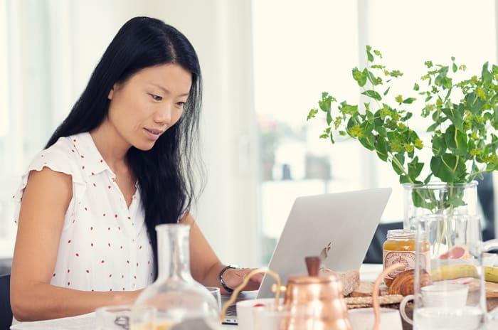 kvinne sitter med en macbook på stuebordet