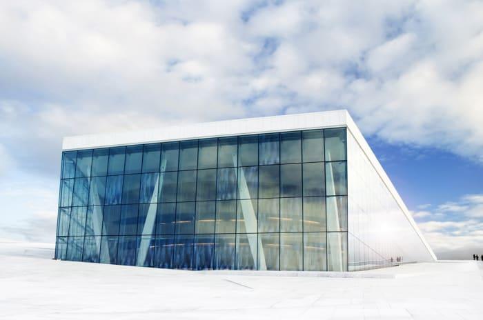 Operahuset i Oslo sett utenfra mot blå himmel og skyer.