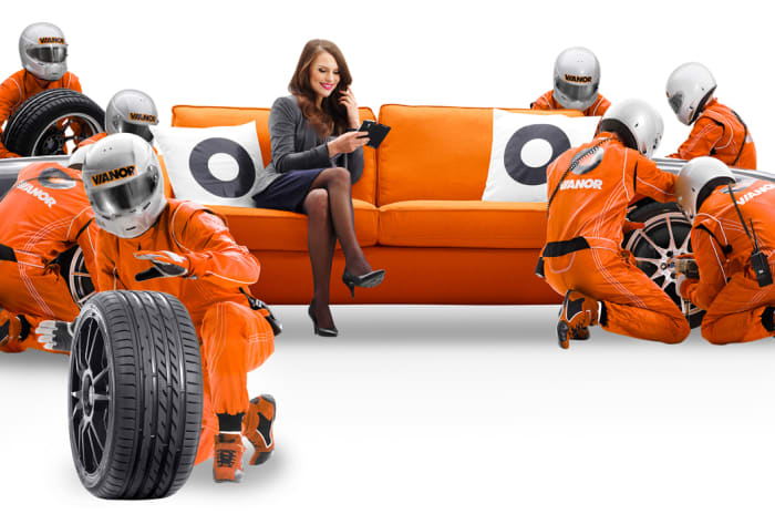 En dame slapper av i en oransje sofa mens menn i oransje arbeidsklær skifter dekk.