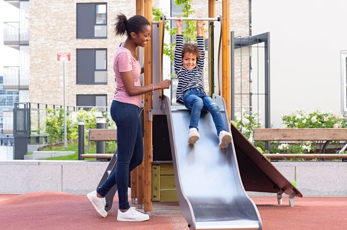 Mor og barn ved en sklie på lekeplass