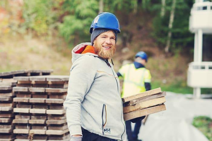 en mann med vernehjelm bærer på treplanker på en byggeplass
