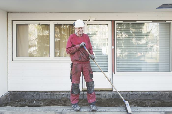 En mann med bygningsklær og hjelm koster et uteområde