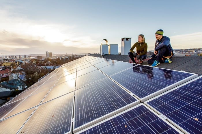 Bildet viser to mennesker sitter på et tak med solceller.