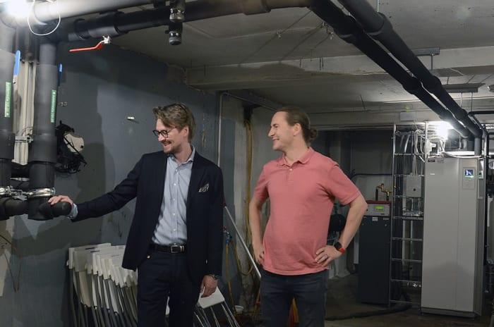 To smilende menn i en kjeller ved et nytt energianlegg