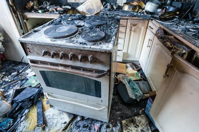 En svartsvidd komfyr i et utbrent kjøkken