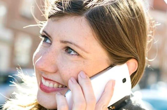 Smilende kvinne som snakker i telefon