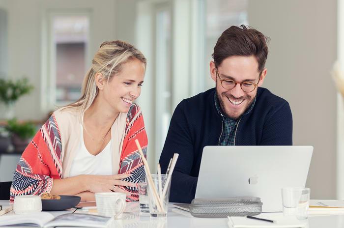 En kvinna och en man framför en dator