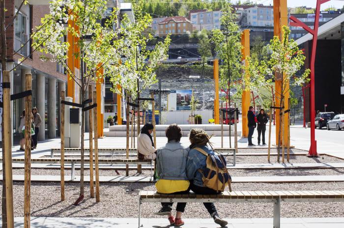 Høstbilde fra torget i Kværnerbyen. To unge jenter sitter på en benk med ryggen til, og ser ut over torget.